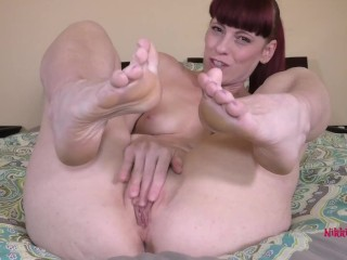 Redhead flashes her toes whle ru her wet pussy