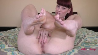 Redhead flashes her toes while rubbing her wet pussy