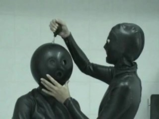 Two Girls In Black Latex Catsuits With Ballhood And Inflateable Mittens