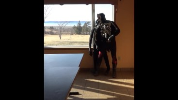 skeleton mask in tights and cowboys boots cums on dummy in front of window
