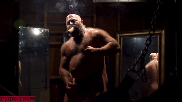 Gay men cigar Hyper masculine muscle hairy bull smoking his cigar in front of the sling