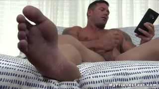Buff stud masturbates with his big soft feet on full display