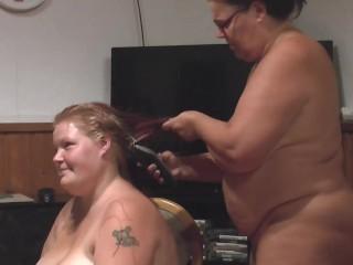 Una ragazza grassa (nuda) taglia i capelli ad un'altra ragazza grassa (nuda)