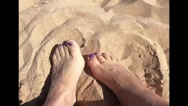 Provocative feet play in the sand, in public.