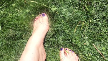 Silky soft young feet playing in freshly cut grass