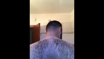 Italian bear in the shower washes his hairy body
