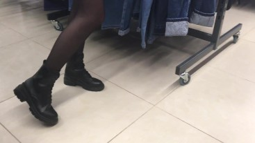 Stranger in black pantyhose in a clothing store