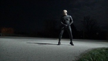 wetsuited guy jerking off in road and in front of house on full moon