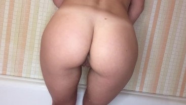 the girl pisses through her fingers. back view