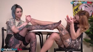Two tattooed lesbians in stockings play hot footsies