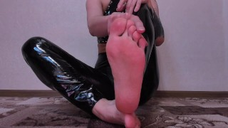 Hot Domme in shiny pvc pants and top strokes her thick strapon barefoot
