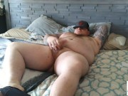 Beefy chubby bear Tyler Nash in a singlet flexes muscles and strokes his beautiful cock.